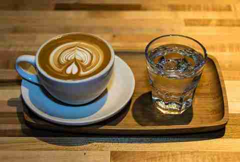 latte art with espresso and a glass of water at Rising Star Coffee