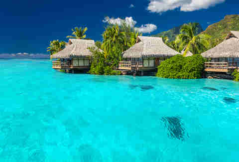 Overwater villas in tropical lagoon of Moorea Island in Tahiti, French Polynesia, with coral reef