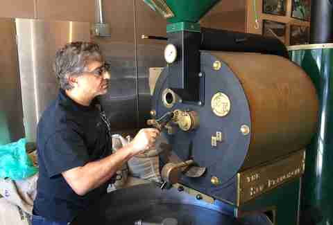 Man grinding coffee beans at Simple Pleasures in Outer Richmond, San Francisco, California