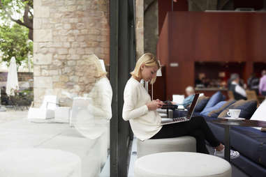 woman sitting in a cafe on her phone and laptop