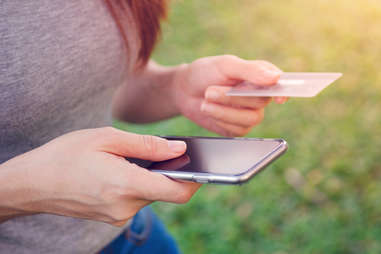 Woman outside holds a smartphone and a credit card