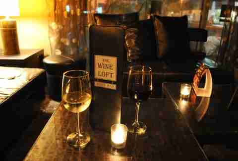 Candlelit table with wine glasses at The Wine Loft