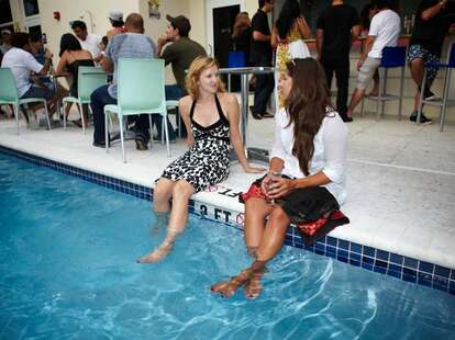Two women day drinking at the pool in Lou's Beer Garden in Miami, Florida
