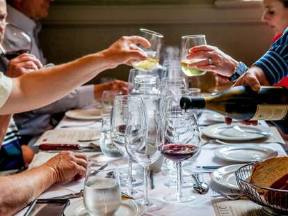 Diners drinking wine and reading menus at Charlotte wine bar