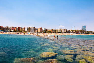Walking along the rocks at the beach in Barcelona, Spain