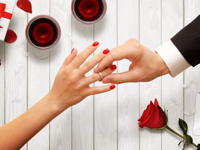 Man putting wedding ring on woman's finger