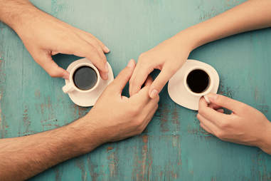 Couple holding hands over cups of coffee
