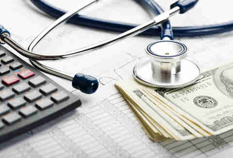 Health insurance forms, money, stethoscope, and calculator