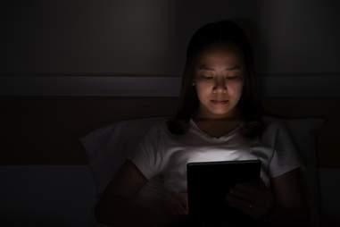 Woman looking at bright iPad in dark bedroom at night