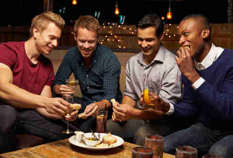 Group of males drinking cocktails and eating appetizers