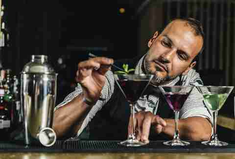 Bartender fixing garnish on purple cocktail