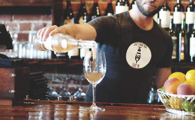 Bartender pouring glass of white wine