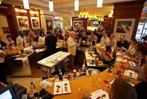 Round table of diners enjoying a tasting paired with wine with host