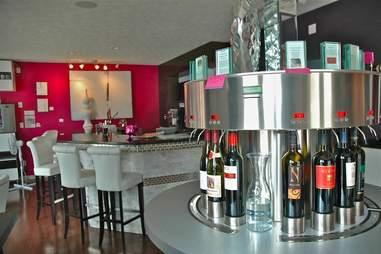 Wine carafe and row of wine bottles inside Shiraz wine cafe
