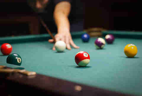 Person playing shooting cue ball in a game of pool
