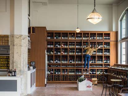 Woman stacking wine at Tofino Wines bar in Inner Richmond, San Francisco, California