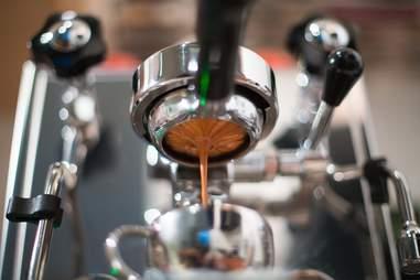 Fresh espresso drinking into espresso cup