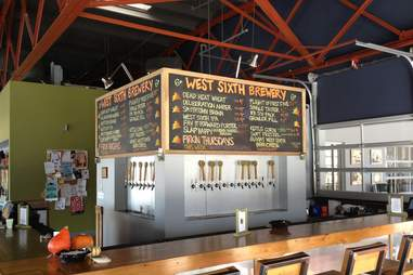 chalkboard menu at West Sixth Brewery with bar and taps