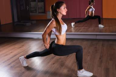 Girl doing lunges inside gym