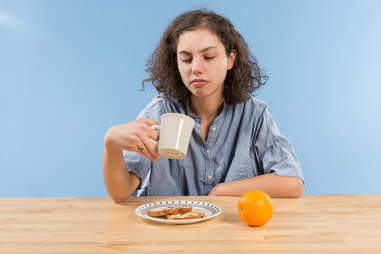 Tired woman looking for more coffee at breakfast