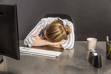 Woman sleeping at her computer on her desk