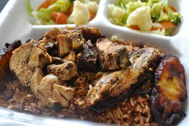 caribbean jerk chicken and vegetables in a takeout container