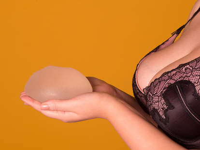 Woman in bra holding a breast implant