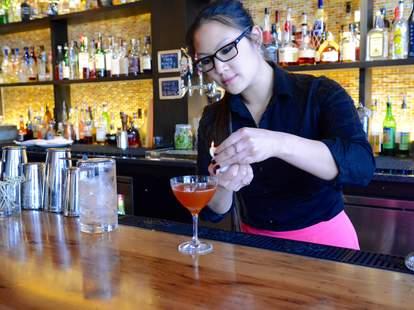 D.C. bartender fixing garnish on orange cocktail