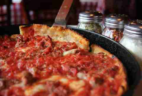 deep dish chicago pizza in man with server, sauce, cheese, dough