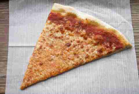 Slice of cheese pizza on thin wax paper