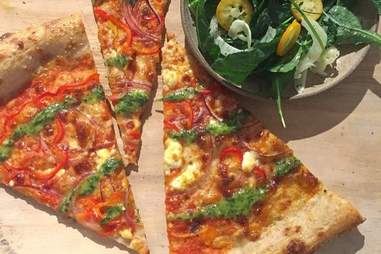 Multiple slices of Mill pizza next to bowl of herbs
