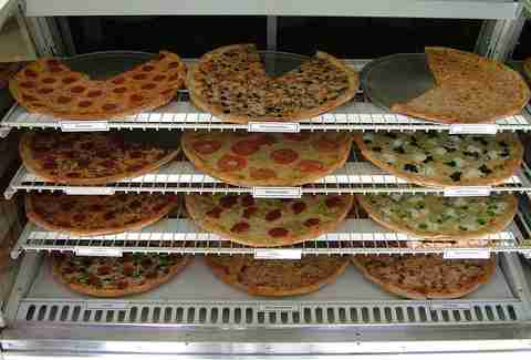 Different types of pizzas laid out at Pizza Shop