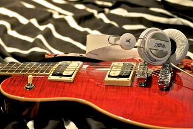 guitar and headphones lying on bed