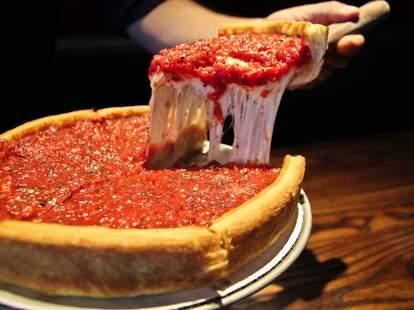 Man cutting slice of Patxis deep dish pizza