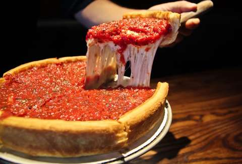 Man cutting slice of Patxis deep dish pizza
