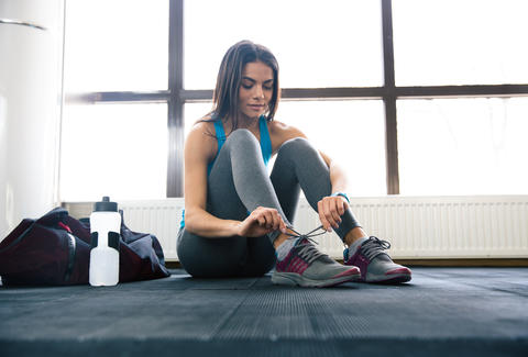 woman lacing up sneakers at gym