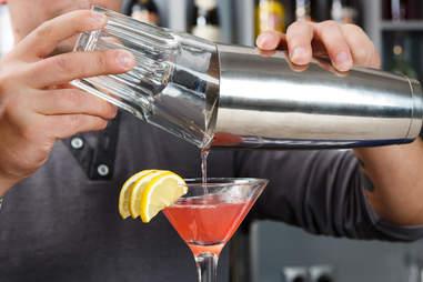 Mixologist finishing pink drink with lemon wedges