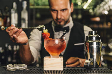 Mixologist placing strawberry garnish on red cocktail