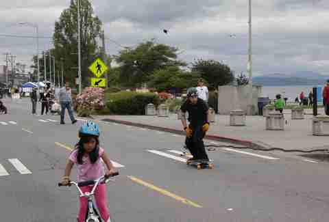 little girl riding a bike and a skateboarder at Alki