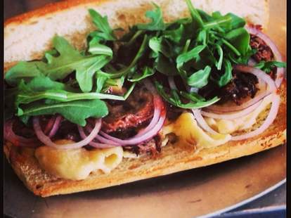 close up of sandwich with argula red onion mac n cheese at court street grocers