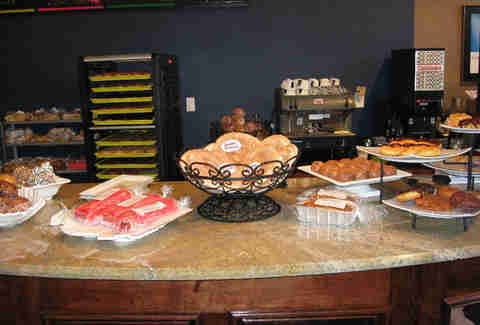 Baskets and platters of packaged and glazed donuts on counter