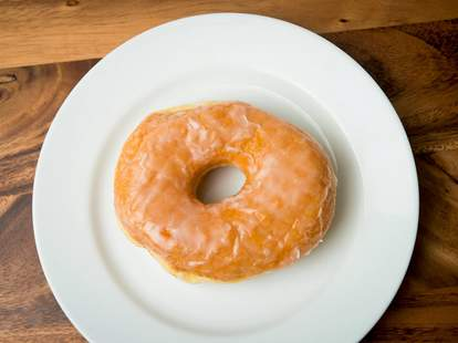 Single glazed donut placed on white plate