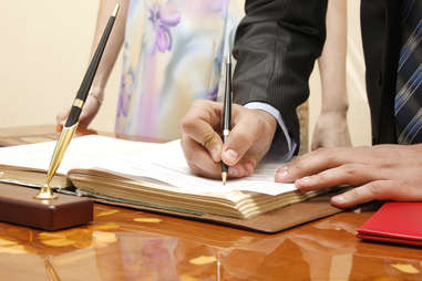 man and woman couple signing a wedding certificate