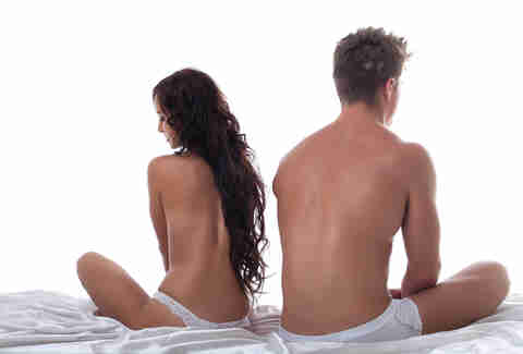 Unhappy naked couple sitting on a bed