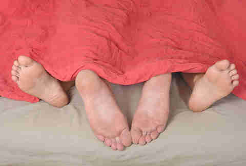 Feet of couple having sex in bed under blanket