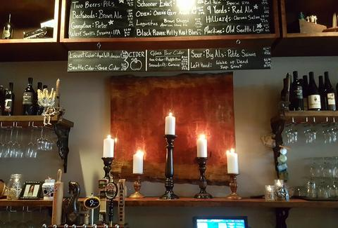 interior of locol wine bar in seattle with candles and menu
