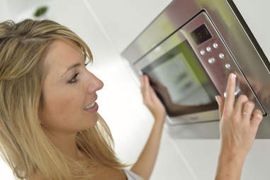 Girl pressing buttons on microwave