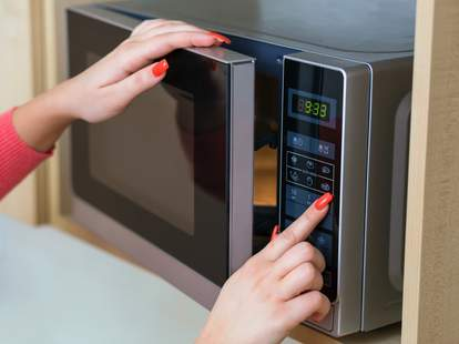 Girl with painted red nails using microwave