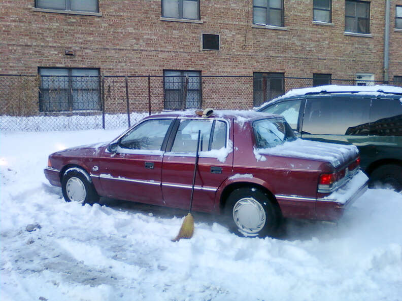 Red car warming up in snowy parking lot