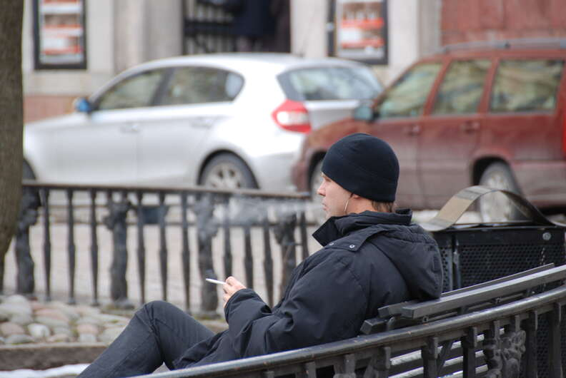 Man smoking cigarette on park bench
